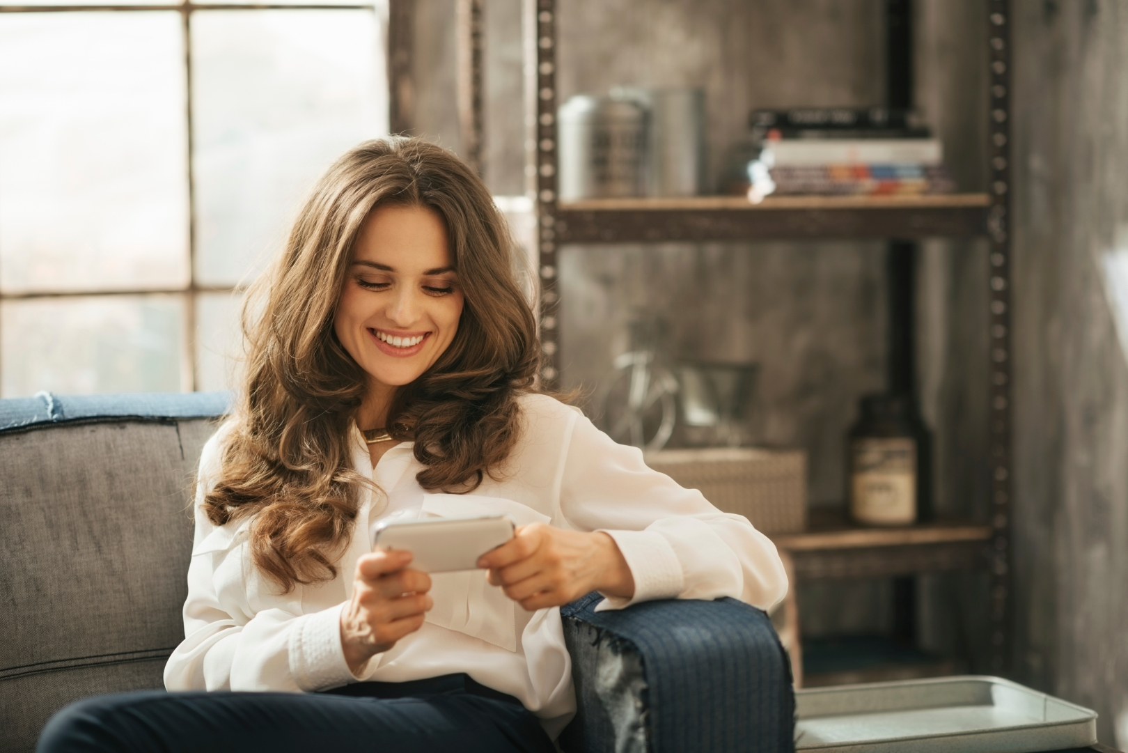 Stylish brunet woman is playing with smartphone sitting on divan in loft apartment